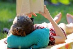 Young girl reading a book in the garden Stock Photo