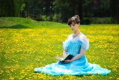 Young girl reading book on the grass Royalty Free Stock Images