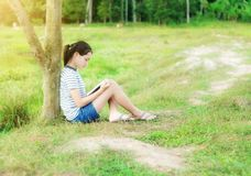 Young girl reading a book in green meadow contryside nature. In evening light vintage style Royalty Free Stock Image