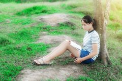 Young girl reading a book in green meadow contryside nature Royalty Free Stock Photography
