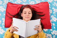 Young girl reading a book on her bed Stock Photos