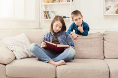 Young girl reading book for her brother. Young cute sister telling fairy tale to her little brother aloud, sitting on couch at home, copy space Stock Photos