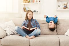 Young girl reading book for her brother. Young girl reading book to her brother. Elder sister telling fairy tale aloud, sitting on couch at home, copy space Royalty Free Stock Images