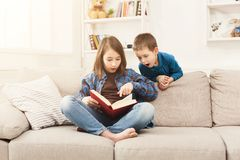 Young girl reading book for her brother. Young girl reading book to her brother. Elder sister telling fairy tale aloud, sitting on couch at home, copy space Royalty Free Stock Image