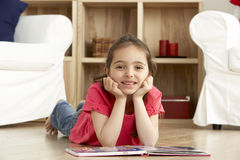 Young Girl Reading Book at Home Stock Photo