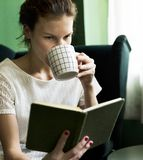 Young girl reading a book at home stock photo