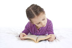 Young girl reading book isolated. Young girl lying down and reading book on white Royalty Free Stock Images
