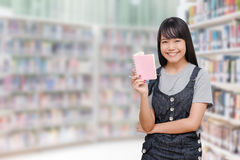 Young girl reading book in library Royalty Free Stock Image