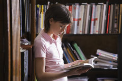 Young Girl Reading Book In Library Royalty Free Stock Photos