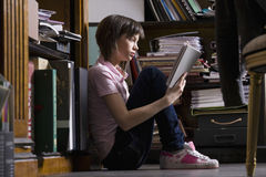 Young Girl Reading Book In Library Stock Photos