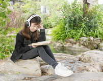 Young girl reading book and listen to music in park Royalty Free Stock Photos