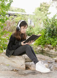 Young girl reading book and listen to music in park Stock Photos