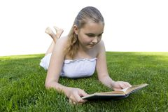 Young girl reading book while lying in grass royalty free stock image