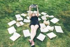 Young girl reading a book while lying in the grass. A girl among the books in the summer garden stock photo