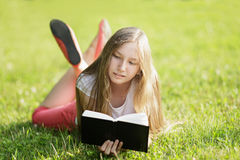 Young girl reading book lying on the grass Stock Photo