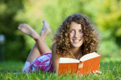 Young Girl Reading Book While Lying On Grass Stock Photos