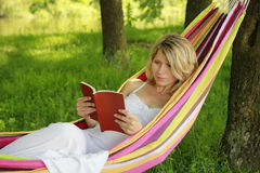 Young girl reading a book while lying on a hammock Royalty Free Stock Photo