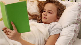 Young girl reading a book while lying in her bed stock video footage