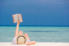 Young girl is reading a book lying on tropical white beach Stock Photos