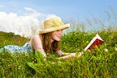 Young girl reading book in meadow Royalty Free Stock Photos