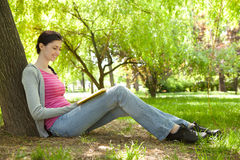 Young girl reading book in nature Royalty Free Stock Photo