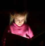 Young girl reading book at night Royalty Free Stock Images