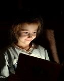 Young girl reading book at night Royalty Free Stock Photo