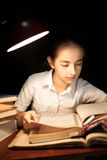 Young girl reading book at night dark at library Royalty Free Stock Image