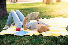 Young girl reading book outdoors Stock Photography