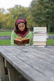 Young girl reading a book in a park Stock Photo
