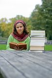 Young girl reading a book in a park Stock Images