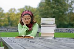Young girl reading a book in a park Stock Image