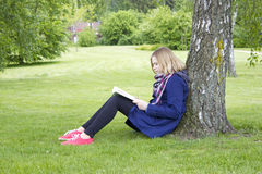 Young girl reading book in park Royalty Free Stock Images
