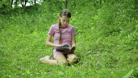 Young girl reading book in the park. Young girl sitting on green grass reading a book in a meadow in the park stock video footage