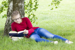 Young girl reading book in park Stock Photo