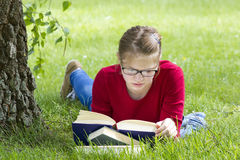 Young girl reading book in park Stock Photos