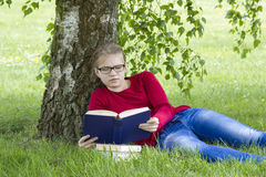 Young girl reading book in park Royalty Free Stock Image