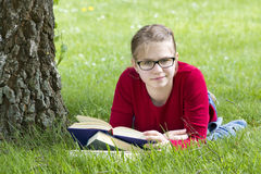 Young girl reading book in park Royalty Free Stock Photo