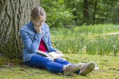 Young girl reading book in park Stock Image