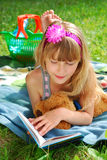 Young girl reading a book on the picnic. Young girl reading a book lying on the blanket on the picnic Royalty Free Stock Photos
