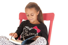 Young girl reading a book in a red rocking chair Stock Images
