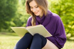 Young girl reading a book and relax in the park Stock Images