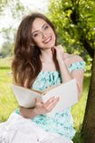 Young girl reading a book and relax in the park Royalty Free Stock Photo