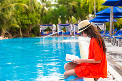 Young girl reading book relaxing in swimming pool Royalty Free Stock Image
