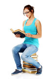 Young girl reading a book sitting on books. Royalty Free Stock Photography
