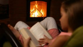 Young girl reading a book sitting in a rocking chair by the fire. In the dark room - camera moves toward the fire, refocusing stock footage