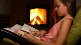 Young girl reading a book sitting in a rocking chair by the fire. In the dark room - closeup stock video