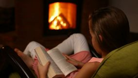 Young girl reading a book sitting in a rocking chair. By the fire in the dark room - closeup stock video