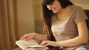 Young girl reading a book and smiling stock video footage