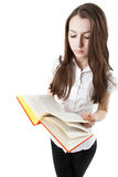 Young girl is reading a book while standing Stock Photos